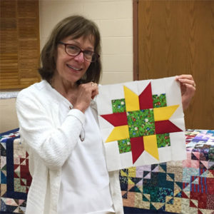 A woman holds a a pattern section