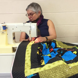 Using a sewing machine to combine sections of a quilt