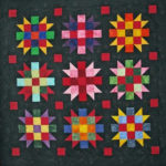 Dark quilt with colorful geometric sections