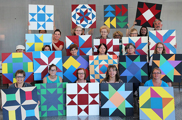a group of women with their barn quilt patterns