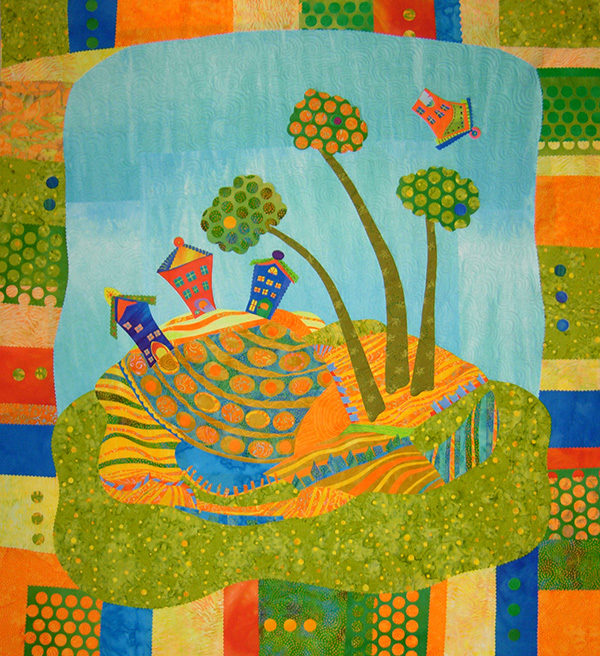 Art quilt of trees, fields and houses on a hill