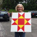 Woman holding a barn quilt pattern