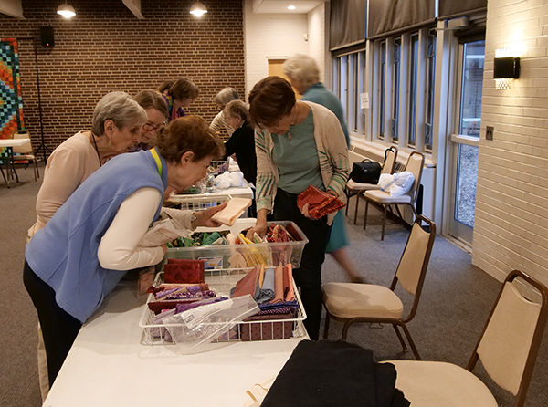 IQI members sorting through fabrics