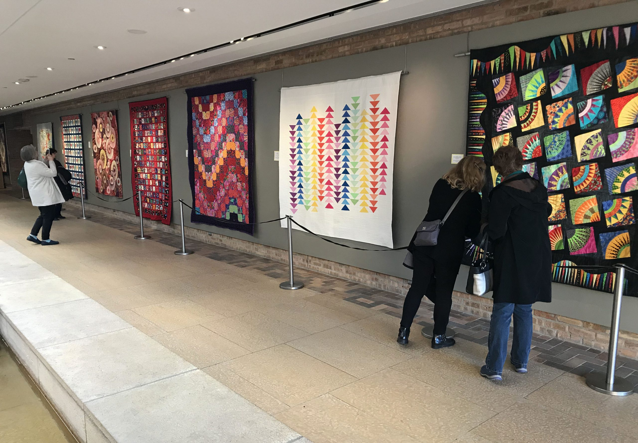 Two women examining a quilt in the Fine Art of Fiber gallery
