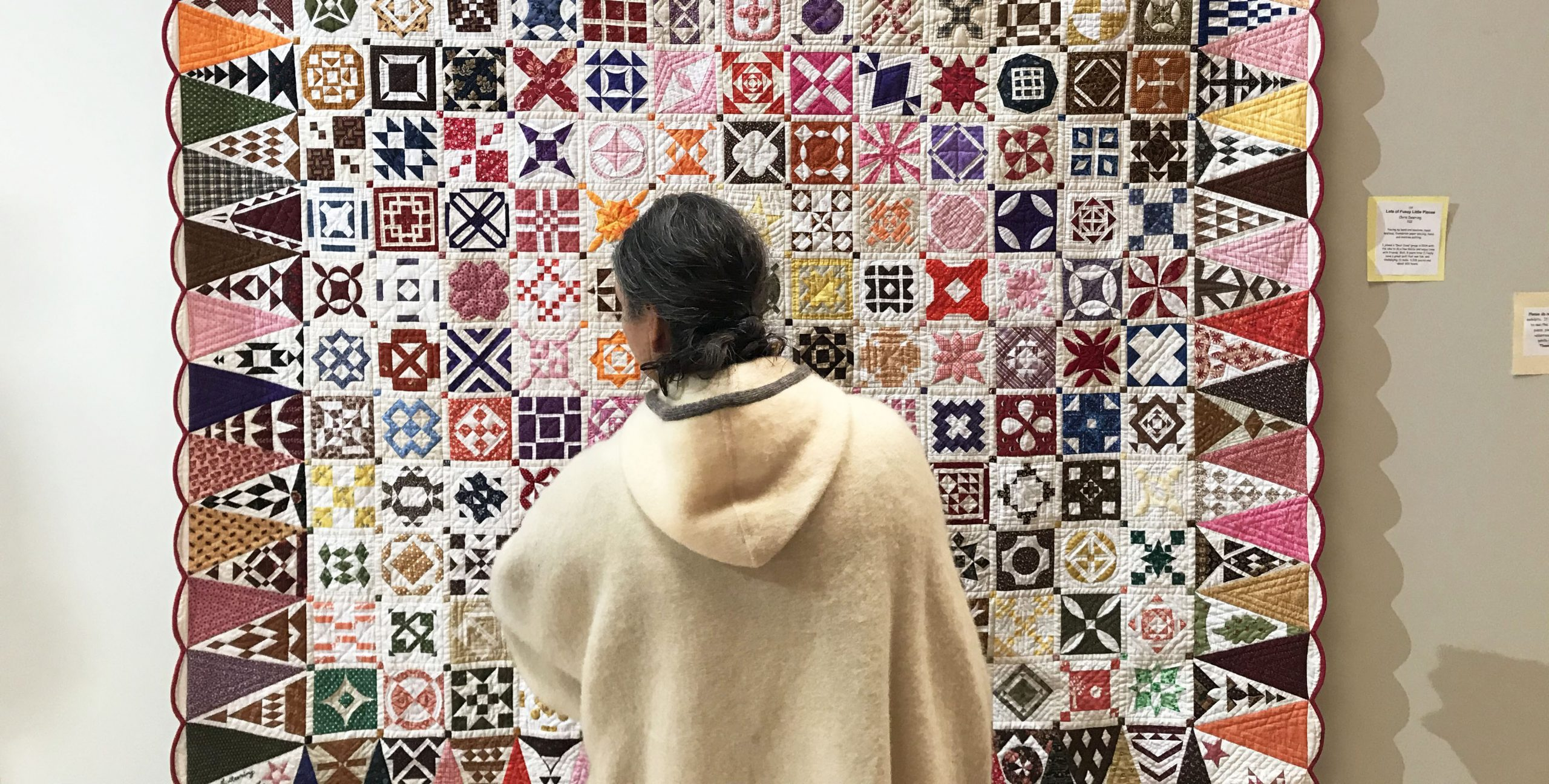 Woman examining a quilt at the Fine Art of Fiber
